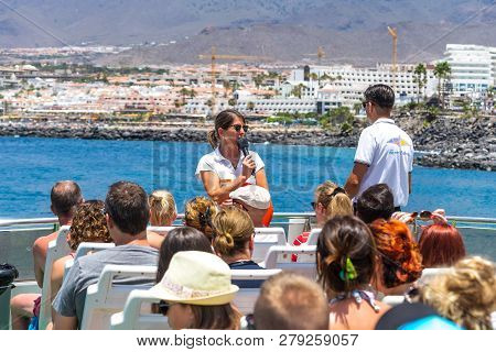 Costa Adeje, Tenerife, Canary Islands, Spain - July 26, 2018: Guide And Tourists On A Ship Against T