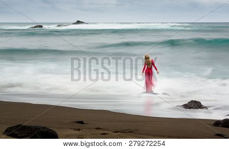 Artistic Fine Art Picture About A Red, Long Dressed Beautiful Blonde Woman, Who Stands On A Beach Ro