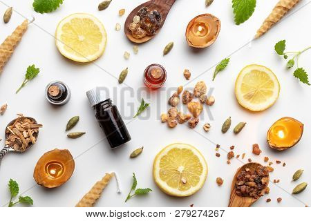 Bottles Of Essential Oil With Frankincense, Cardamon, Melissa, Fresh Lemon And Other Ingredients On