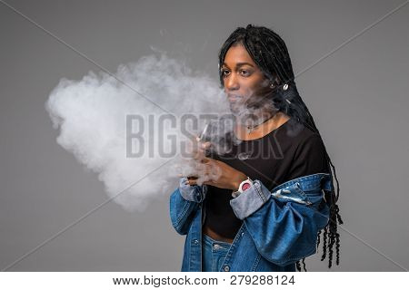 Young African Woman Holding And Vaping An Electronic Cigarette, E-cig, Ecigarette With Smoke Cloud I