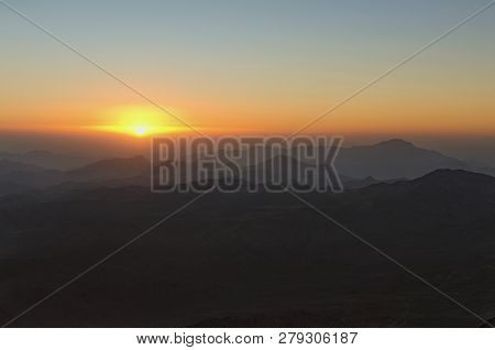 Amazing golden sunrise in the mountains. White sun disk on the mountains. View from Mount Sinai (Mount Horeb, Gabal Musa, Moses Mount). Sinai Peninsula of Egypt. poster