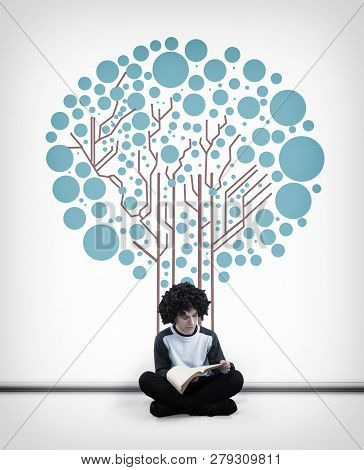 Young Man Reading A Book In Front Of A White Wall Drawn With A Circuit Board Tree.