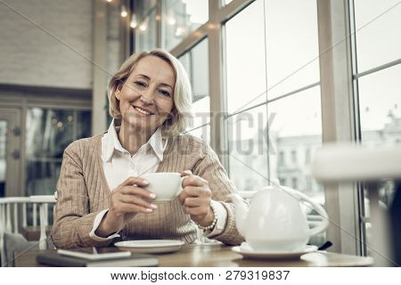 Stylish Mature Woman With Facial Wrinkles Drinking Tea In Cafeteria