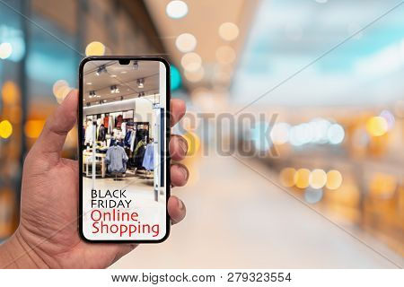 Hand Holding Smartphone With Blur Interior In Mall. Black Friday Shopping App In A Mobile Phone Scre