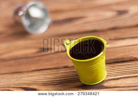 Full Green Bucket Of Black Coffee Near Empty Zinked Metal Bucket With Handle On Old Worn Wooden Tabl