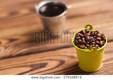 Full Zinked Bucket Of Black Coffee Near Green Metal Bucket With Handle Full Of Roasted Coffee Beans