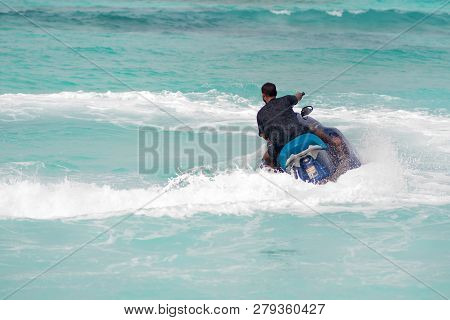 Ride On A Jetski. Man On A Water Scooter Makes A Turn. Pure Blue Water
