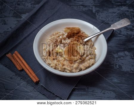 A plate of porridge with a sprinkling of cinnamon and banana circles. A teaspoon in a plate with each, a black cotton napkin. Nearby are cinnamon sticks. poster