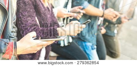 Multicultural friends group using smartphone at university college backyard break - People hands addicted by mobile smart phone - Technology concept with always connected millenials - Bright filter poster