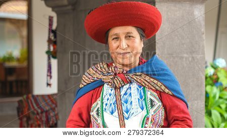 Cusco, Peru - 01.03.2019 Native Peruvian Woman In Traditional Colorful Dress With Red Hat In Sacred