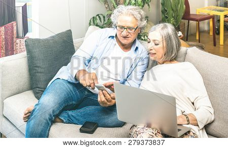Senior Retired Couple Using Laptop Computer At Home On Sofa - Elderly And Technology Concept With Ma