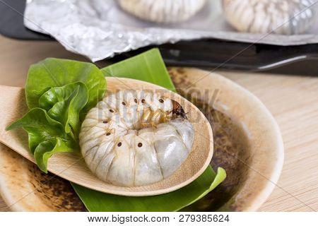 Grub Worms or Coconut Rhinoceros Beetle. Insects food for eating larvae fried or baked in spoon with vegetable on plate and on baking tray is good source of protein which edible. Entomophagy concept. poster