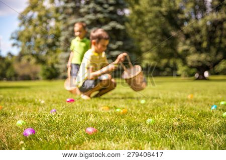 Kids Looking For Easter Eggs In The Park. Easter Eggs Hunt. Blurred Silhouettes Children With Basket