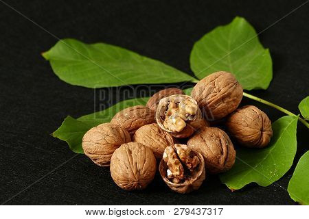 Dry Shelled Walnut And Green Walnut Leaves, On Black Background, Dry Shelled Walnut And Green Walnut