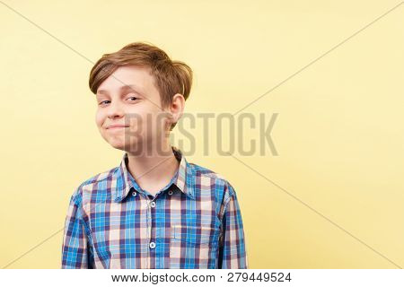 Mocking Jeering Scoffing Boy With Ironical Smile Over Yellow Background, Advertisement, Banner Or Po