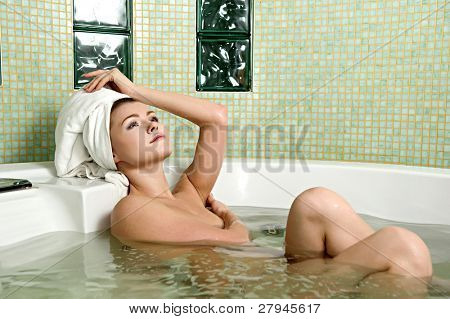 beautiful woman in a bathroom with a towel on a head