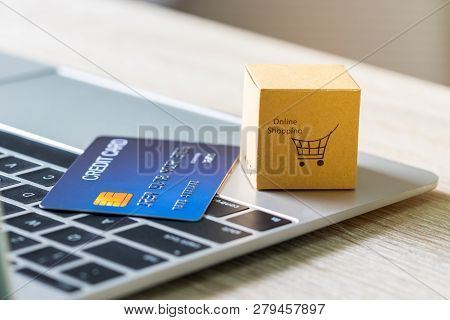 Cardboard Box With Text Online Shopping And Mock Up Of Credit Card On Laptop Keyboard. Consumer Can