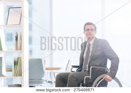 Portrait of disabled businessman on wheelchair at modern office