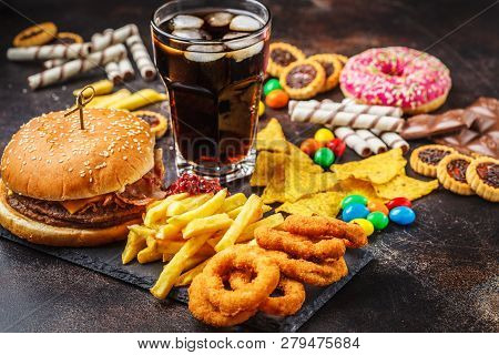 Junk Food Concept. Unhealthy Food Background. Fast Food And Sugar. Burger, Sweets, Chips, Chocolate,