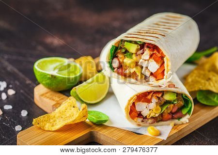 Grilled Burritos Wraps With Chicken, Beans, Corn, Tomatoes And Avocado On A Wooden Board, Dark Backg