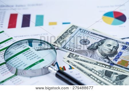 Magnifying Glass And Us Dollar Banknotes On Charts Graphs Spreadsheet Paper. Financial Development,