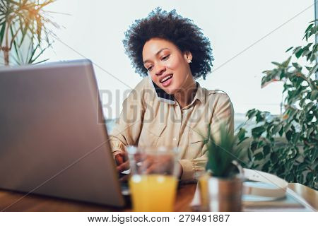 Smiling Young African Female Entrepreneur Sitting At A Desk In Her Home Office Working Online With A