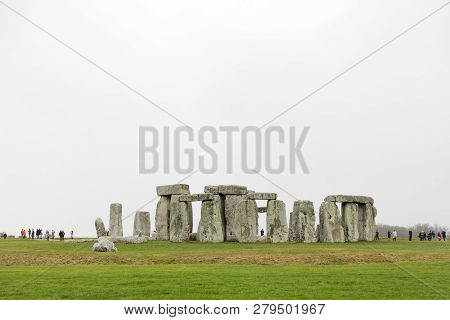 Amesbury, Great Britain - Dec 23, 2018: Tourists Watching The Stone Monument Stonehenge A Cloudy Day