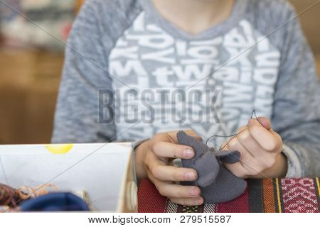 Handicraft Courses. The Girl Is Learning To Sew. A Girl With Threads And A Needle. Creation. Little