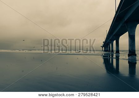 New Brighton Pier, Long Pier Disappearing Into Sea At Low Tide On Wet Calm Day. Christchurch New Zea