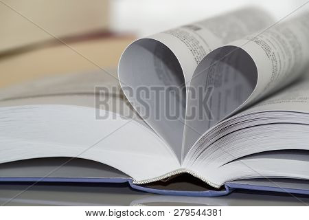 Close-up Of Heart Shape From Paper Book. Love For Reading