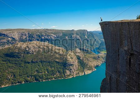 Hiker Standing On Preikestolen And Looking On The Fjerd, Preikestolen - Famous Cliff At The Norwegia