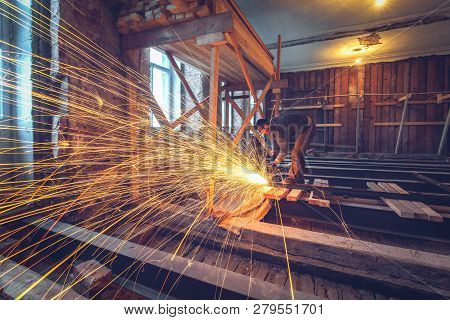Worker Is Using Angle Grinder With Fountain Of Sparks In Apartment That Is Under Construction, Remod