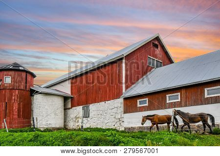 A Colorful Sky Above A Vintage Barn As  Horses Graze On A Thoroughbed Horse Farm In Finland