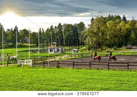 Two Female Equestrians Ride Thoroughbred Horses On A Horse Farm In Late Afternoon At The Town Of Sip