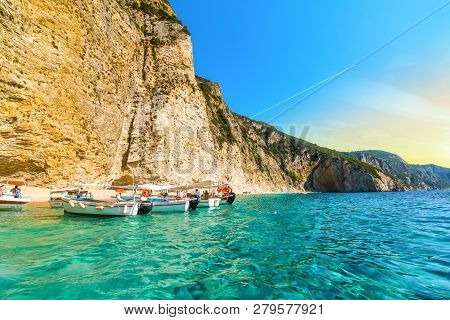 Corfu, Greece - September 16 2018: Boats Line Up At The Shoreline In The Clear Waters Off The Sandy