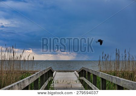The pier in Currituck Heritage Park in Corolla on the Outer Banks in North Carolina is a popular tourist attraction.  This location is on the sound in this historic area of the OBX.