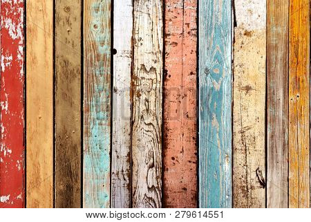 Texture of ancient wood with cracked paint of white, red, orange, yellow, cyan and  blue color