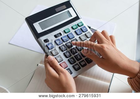 Close-up Of Accountant Using Calculator While Examining Report. Unrecognizable Woman Sitting At Tabl