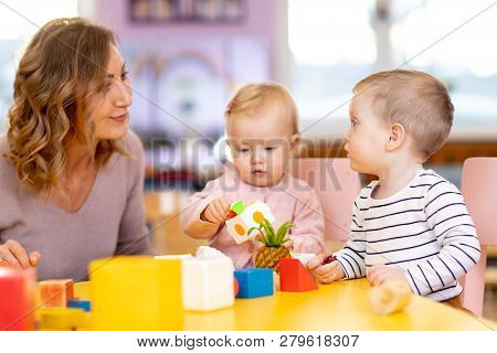 Nursery Babies Playing Toys With Teacher In Playroom At Preschool Or Kindergarten. Education Concept