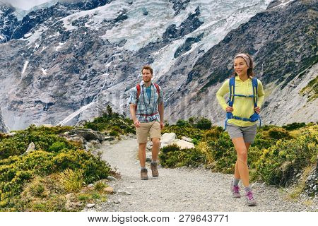 New Zealand tourists people tramping with backpacks on Mount Cook / Aoraki Hooker valley travel. Backpacking hikers hiking on Hooker Valley Track. Couple walking. poster