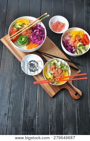 Poke bowls with fresh salmon, crystal noodles, radish, avocado, sweet pepper, cucumber, sesame seeds, red cabbage. Organic food. Fresh seafood recipe. Food concept poke bowl on wooden background poster