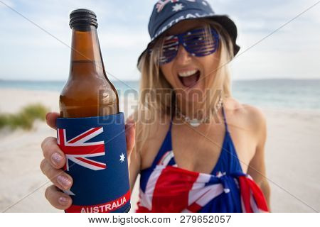Australian Woman On The Beach Holding Or Offering A Beer And Cheerfully Smiling.  Focus To Bottle Wh