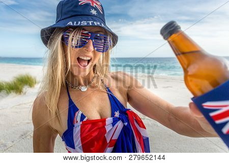 Happy Patriotic Woman On The Beach Holding A Cold Beer Or Other Beverage.  Australian Culture, Beach