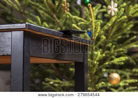 Mobile Phone Is Dangerous Lies On The Edge Of The Table On Christmas Tree Background, Carelessly Lef