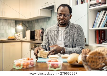 Caring Father Wearing Glasses Cooking Sandwiches For Family Trip