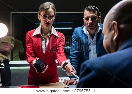 Low-angle view of two persuasive investigators trying to obtain a signed confession from a reluctant suspect at the police station