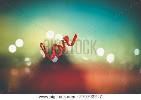 Photo of a word love written on the glass by red lipstick, love message on Valentine's day, love and passion concept