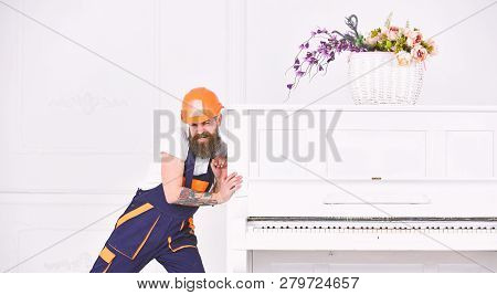 Man With Beard Worker In Helmet And Overalls Pushes, Efforts To Move Piano, White Background. Heavy