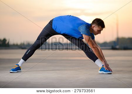 Young Male Runner Stretching and Preparing for Run at Sunset. Healthy Lifestyle and Active Sport Concept.
