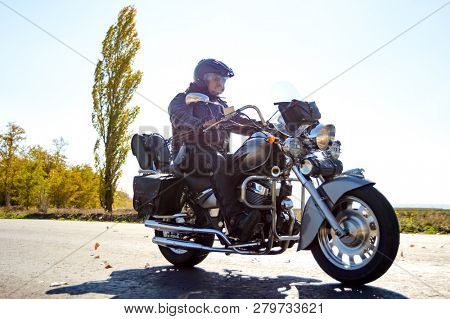 Motorcycle Driver Riding Custom Chopper Bike on an Autumn highway. Adventure Concept.